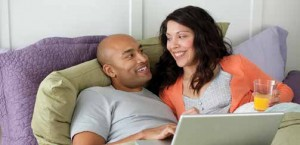 Couple in bed with computer and orange juice